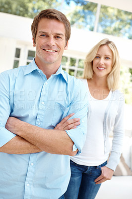 Buy stock photo Smiling handsome man standing indoors with his wife behind him