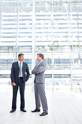 Buy stock photo Two businessmen having a lively discussion in the lobby of their office
