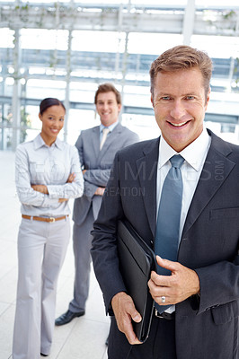 Buy stock photo An experienced business leader standing with his colleagues blurred in the background