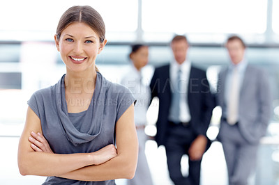 Buy stock photo An ambitious businesswoman standing with her colleagues blurred in the background