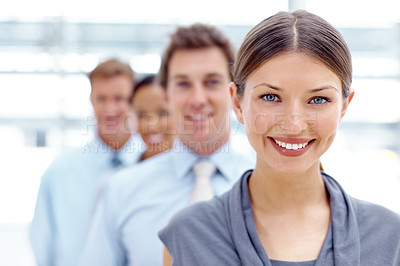 Buy stock photo A pretty young businesswoman smiling at you with colleagues blurred in the background