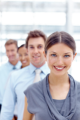 Buy stock photo A pretty young executive smiling with her colleagues blurred in the background
