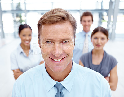 Buy stock photo Portrait of a smiling executive with his business team standing behind him
