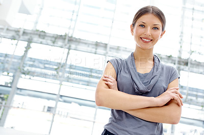 Buy stock photo Portrait of a pretty young businesswoman crossing her arms and smiling alongside copyspace