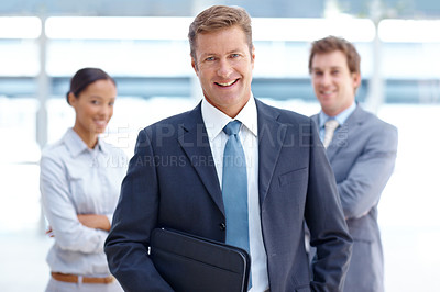 Buy stock photo A handsome businessman smiling at the camera with two colleagues in the background