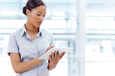 Buy stock photo A gorgeous young businesswoman working on a digital tablet