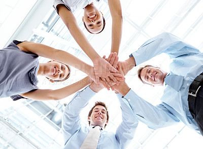 Buy stock photo Low angle portrait of a group of young businesspeople putting their hands together in a show of team spirit