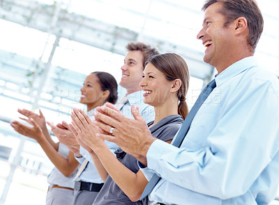 Buy stock photo A group of businesspeople applauding someone while standing in a row