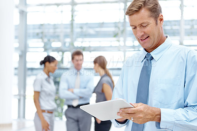Buy stock photo A smiling businessman working on his digital tablet with his colleagues in the background