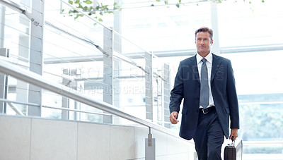 Buy stock photo A handsome businessman walking with his suitcase