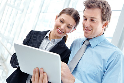 Buy stock photo An attractive young business couple working on a digital tablet