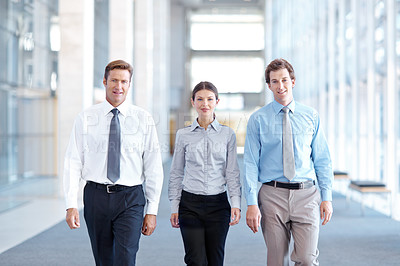 Buy stock photo Three businesspeople walking together towards the camera