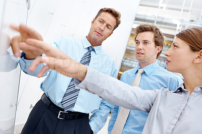 Buy stock photo A mature businessman showing his colleagues something on a white board in their office