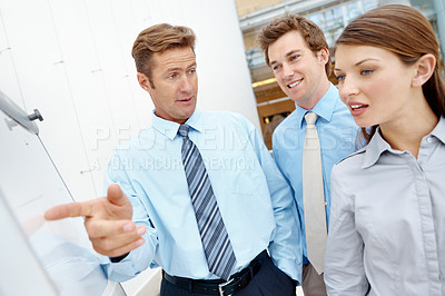 Buy stock photo A mature businessman pointing out something on a white board to his co-workers