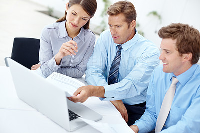 Buy stock photo A group of businesspeople working together on a laptop
