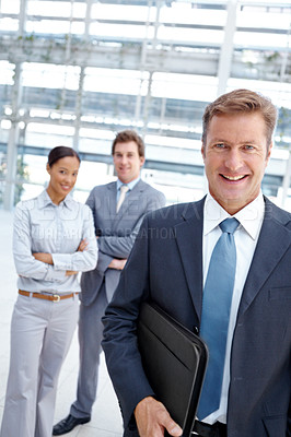 Buy stock photo Mature businessman holding a document folder and smiling with his coworkers behind him