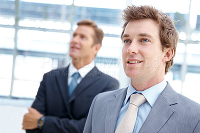 Buy stock photo Two handsome businessmen standing together and looking away