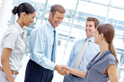 Buy stock photo Two businesspeople smiling and shaking hands while their coworkers look on