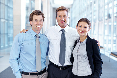 Buy stock photo Three businesspeople standing together and smiling