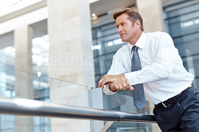 Buy stock photo Mature businessman leaning against a glass railing and looking away thoughtfully