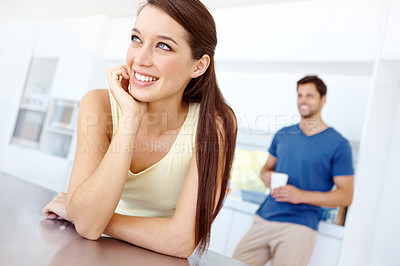 Buy stock photo Pretty woman leaning on her kitchen counter daydreaming with her boyfriend in the background