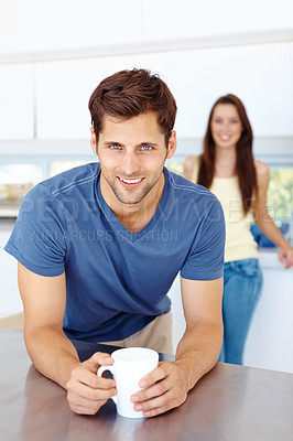 Buy stock photo Portrait of a happy man leaning on his kitchen counter with a woman in the background