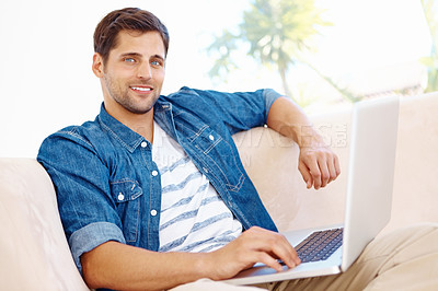 Buy stock photo Portrait of a relaxed smiling man sitting on the couch with a laptop on his lap
