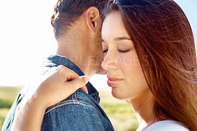 Buy stock photo A pretty woman with her eyes closed hugging her boyfriend outside