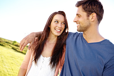 Buy stock photo A couple looking at each other with affection while standing in a field