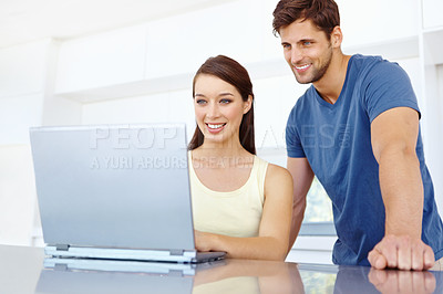 Buy stock photo Shot of a handsome young couple working on a laptop together in their kitchen