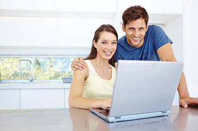Buy stock photo Portrait of a handsome young couple working on a laptop in their kitchen