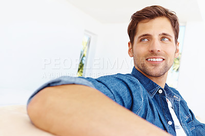 Buy stock photo Shot of a happy-looking young man sitting on a sofa in the living room and looking out of frame
