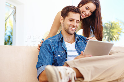 Buy stock photo Shot of a good-looking young couple working on a digital tablet while sitting on a sofa in their living room
