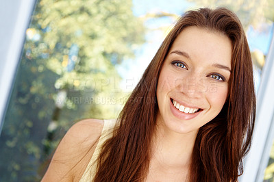 Buy stock photo Close up portrait of an attractive young woman standing in front of some windows outside