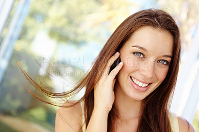 Buy stock photo Close up portrait of an attractive young woman talking on a cellphone outside in front of some windows