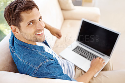 Buy stock photo High angle portrait of a handsome young man sitting on a sofa and using a laptop