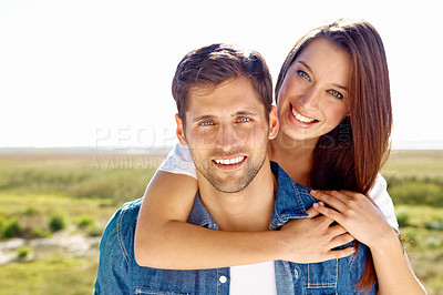 Buy stock photo Portrait of a young woman hugging her husband from behind while on a day out together