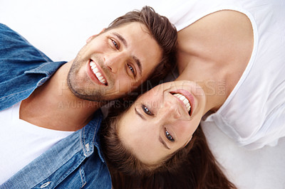 Buy stock photo High angle close up portrait of a happy young couple lying on the floor and smiling up at the camera