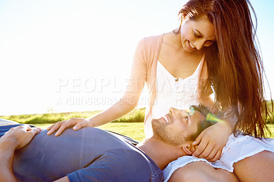 Buy stock photo Shot of a young man lying on his girlfriend's lap while they enjoy the sunshine