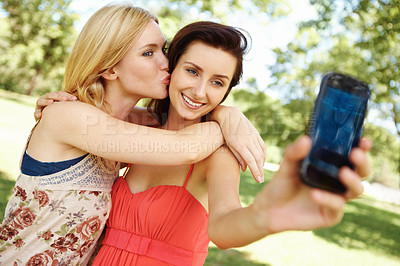 Buy stock photo Girl friends sitting in the park posing for a picture being taken on their cell-phone