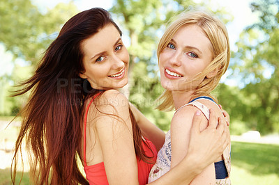 Buy stock photo Portrait of two girl friends happily smiling and hugging each other in the park