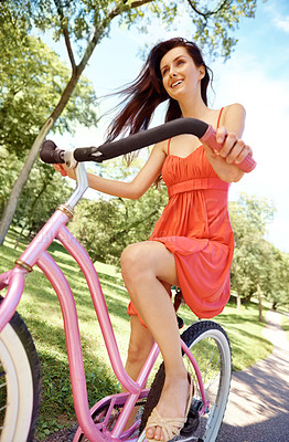 Buy stock photo A pretty brunette on her bicycle in the park