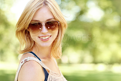 Buy stock photo Portrait of a beautiful young woman wearing sunglasses in an outdoor environment