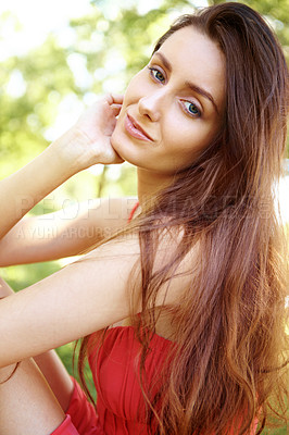 Buy stock photo Portrait of a beautiful young woman sitting on the grass in a park