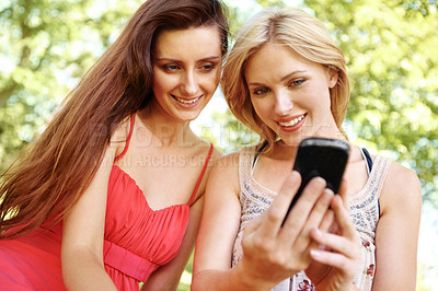 Buy stock photo Two beautiful friends using a cellphone in a park