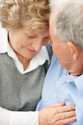 Buy stock photo A romantic senior couple with their heads against one another