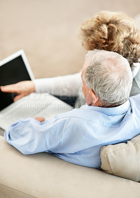 Buy stock photo Rearview of a senior couple sitting on the couch at home while the wife points at a blank laptop screen