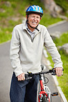 Sporty mature man wearing helmet with bicycle in countryside