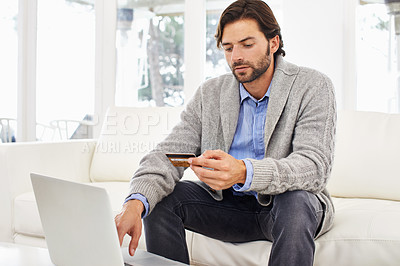 Buy stock photo A handsome man using his credit card to do online shopping