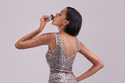Buy stock photo Studio shot of a gorgeous  young woman eating a chocolate cupcake against a gray background